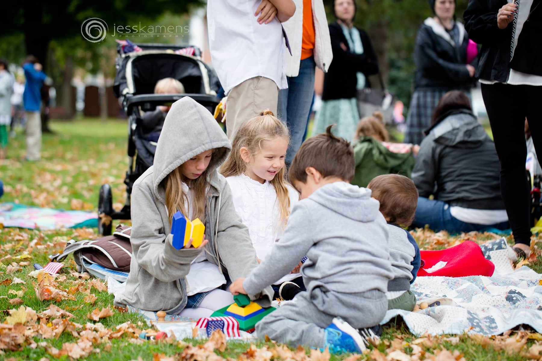 children play on a blanket together in a park