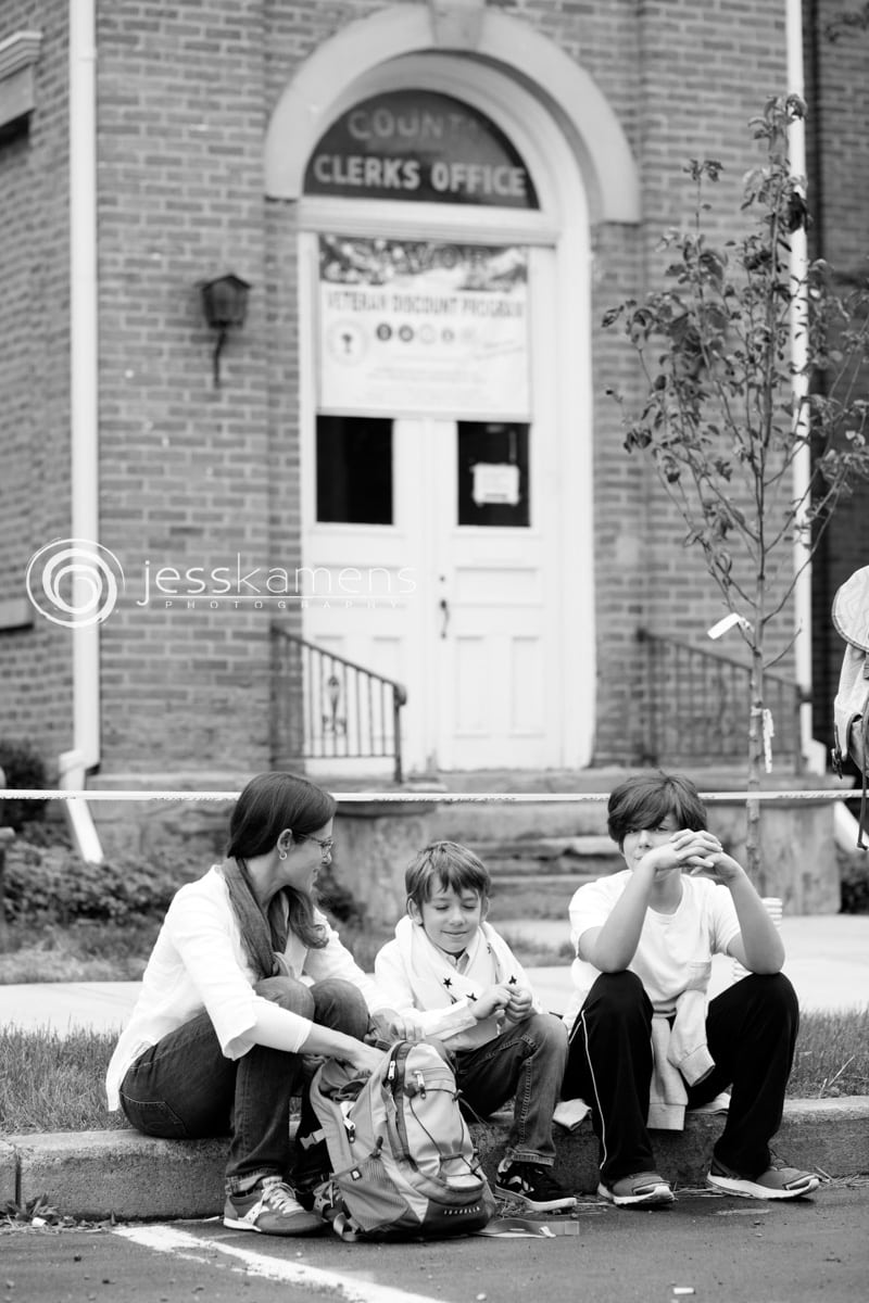 a mother and her children wait dressed in white outside the courthouse