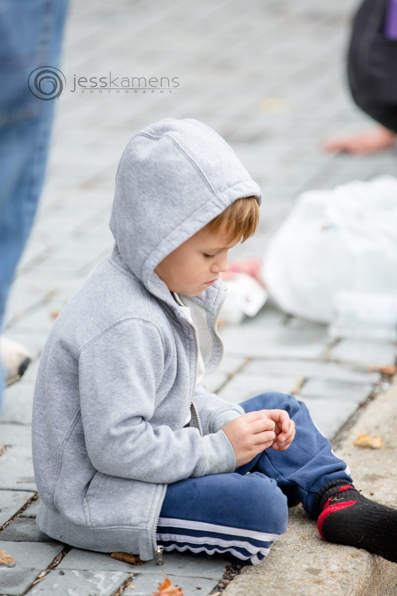 a child sits on the curb and waits