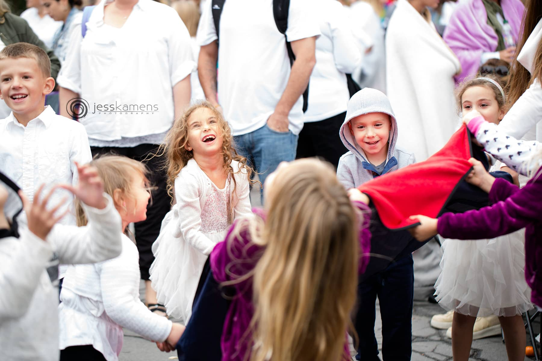homeschooled children play in a circle with a parachute and a ball