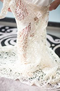 bride putting on her lace wedding gown