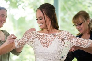 friend and mother of the bride helping her get dressed before her wedding