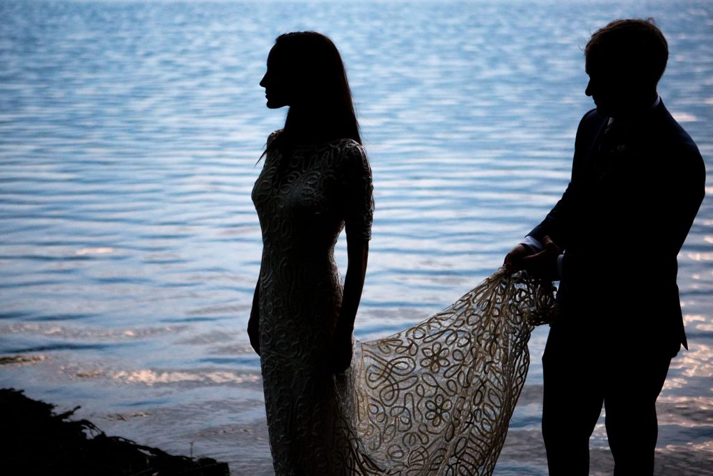 silhouette of bride and groom against the water of irondequoit bay at the end of a two-day wedding