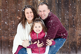 a family hugging in the snow during a snow session in Rochester