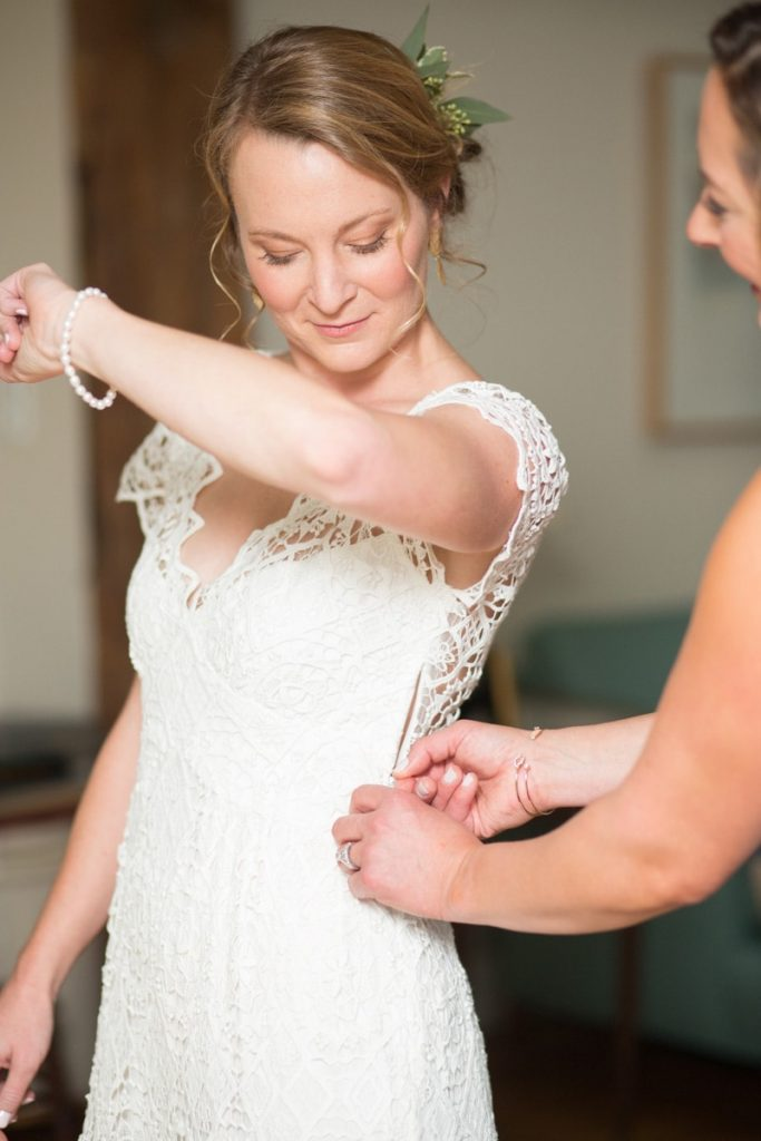 bride is getting zipped by her maid of honor