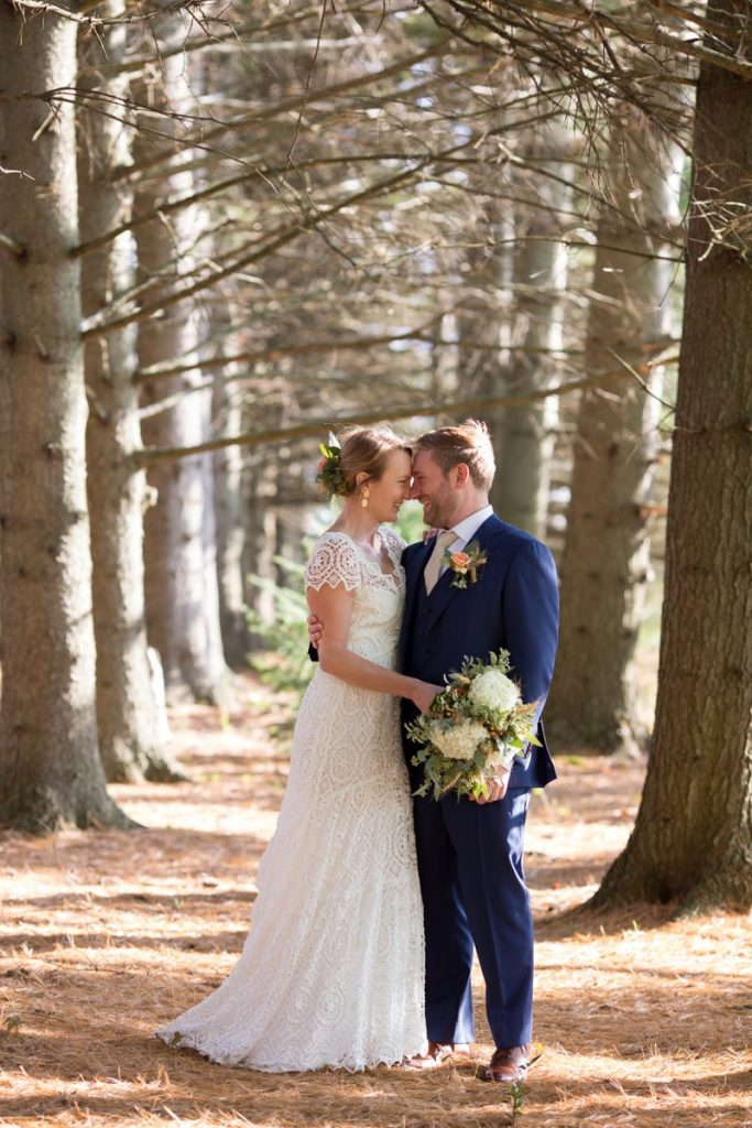 husband and wife at their wedding have a portrait in the woods