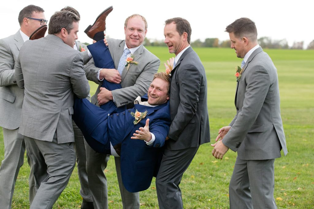 groomsmen pick the groom up and laugh