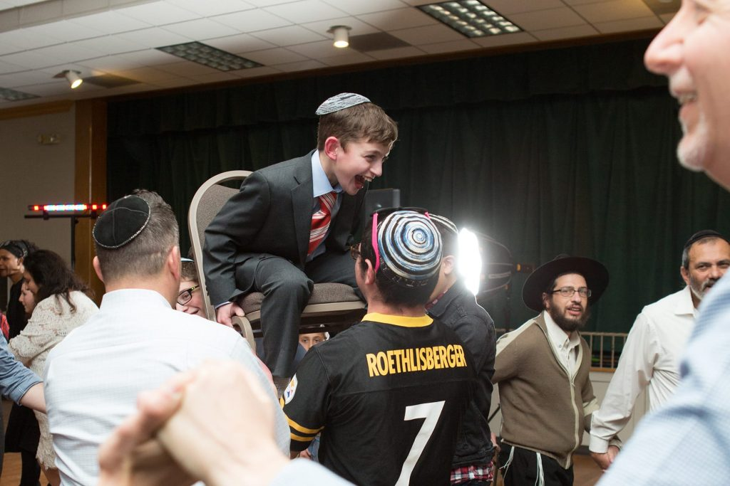 bar mitzvah boy is lifted on the chair while dancing the hora with his family