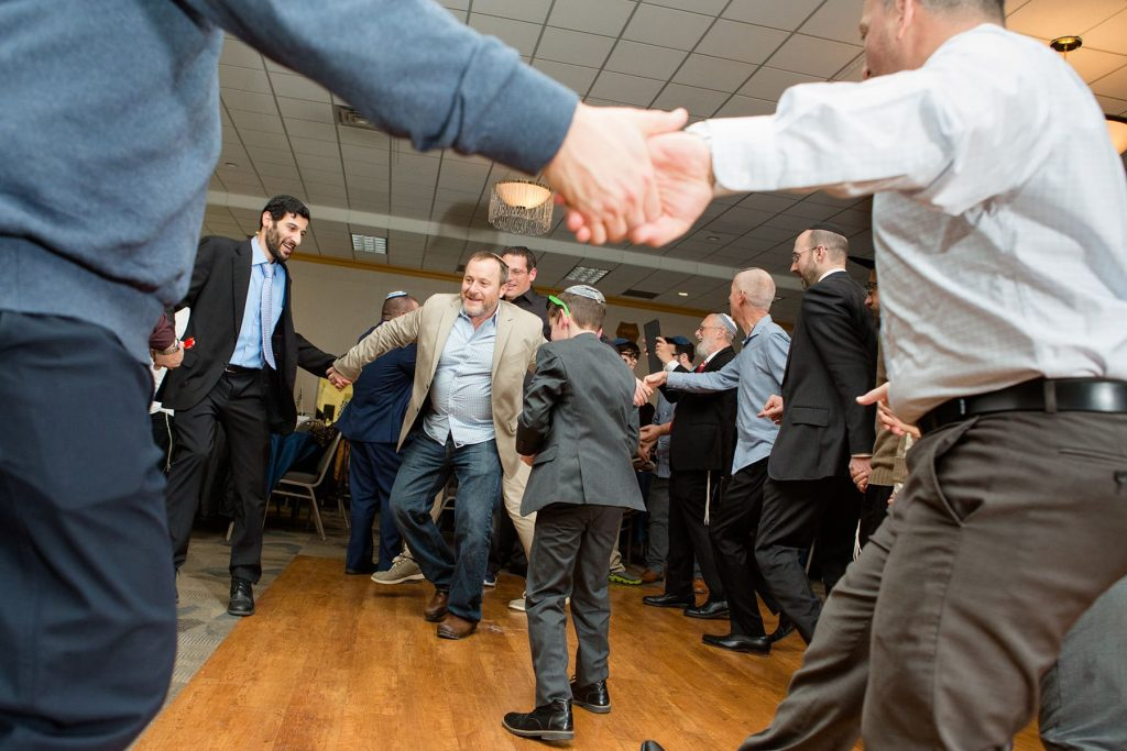 men dance the hora together during a bar mitzvah in rochester ny