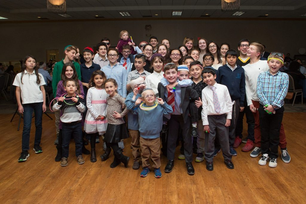 children smiling together at a mitzvah at congregation beth shalom