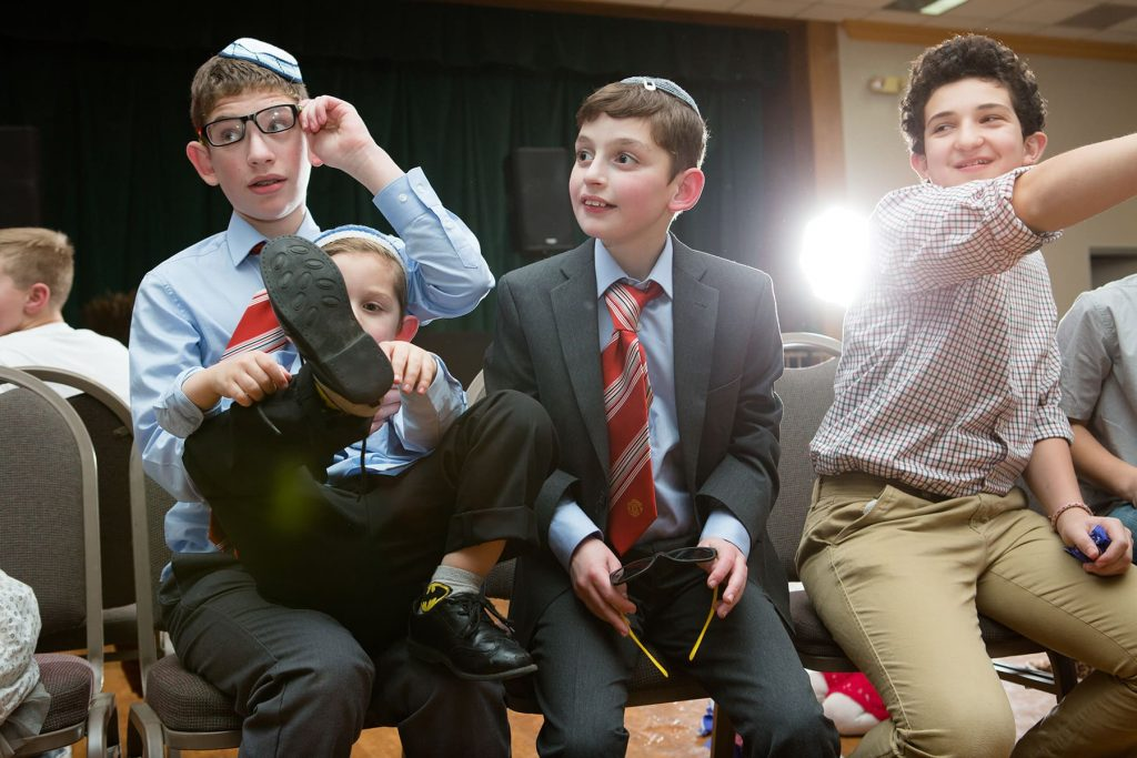 4 children sit in chairs while playing fun games at a mitzvah celebration