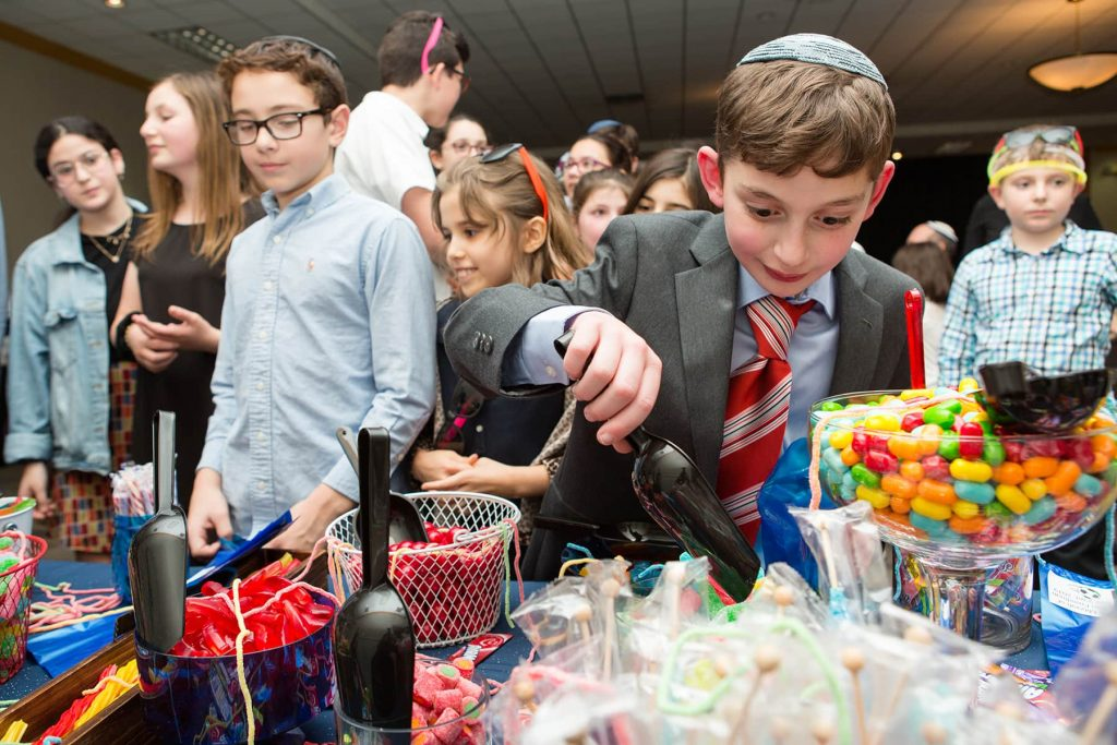 boy loads up his bag full of candy at his party