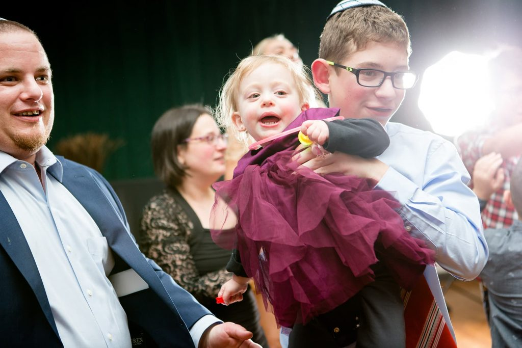 mitzvah photographer in Rochester captures a baby in her brother's arms dancing