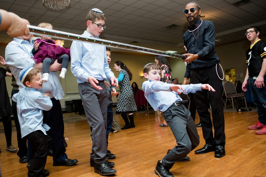 bar mitzvah boy doing the limbo with his siblings