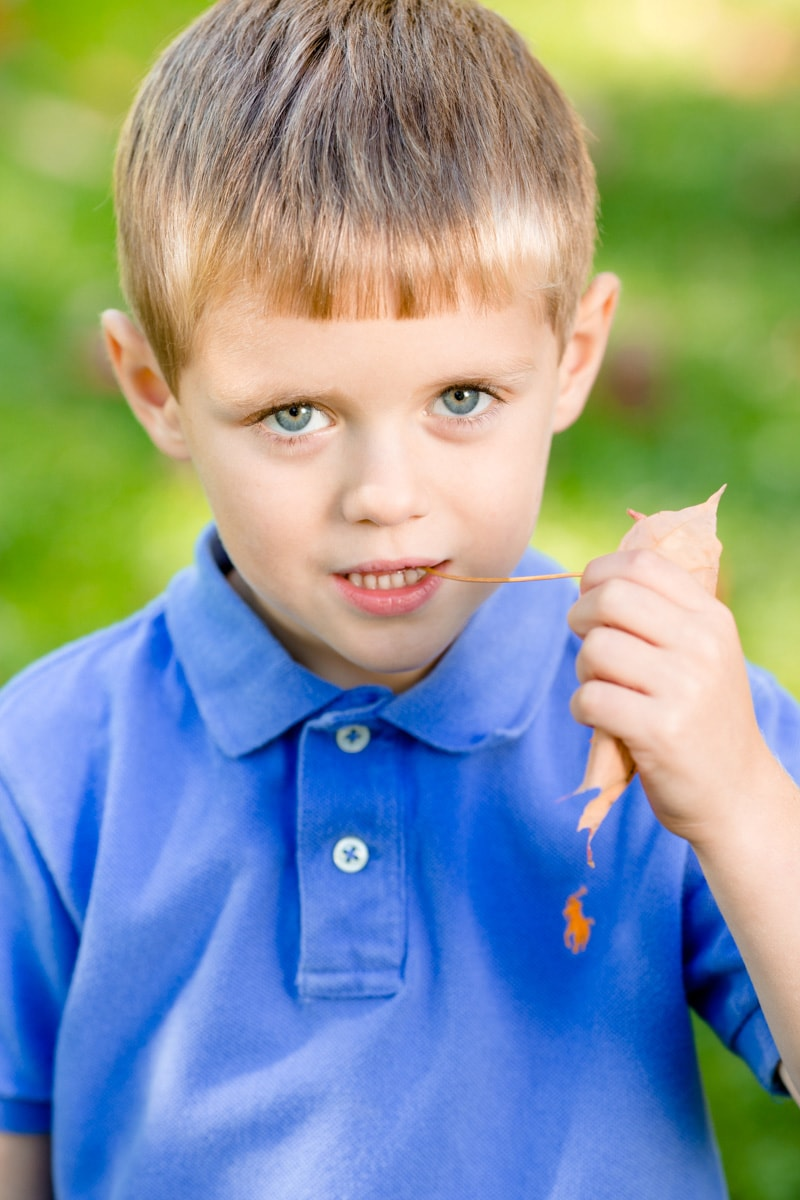 boy eats leaf and looks at a camera