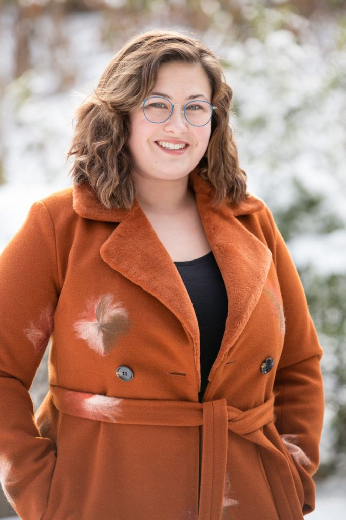 a business headshot of a young woman in an orange coat